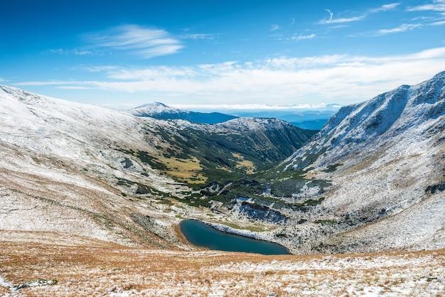 Красивое озеро в зимних горах. пейзаж с солнцем и снегом