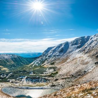冬の山々にある美しい湖。太陽と雪のある風景
