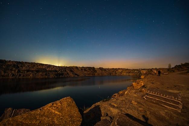 별이 있는 아름다운 밤하늘을 배경으로 광산에서 열심히 일한 많은 돌 폐기물로 둘러싸인 아름다운 호수