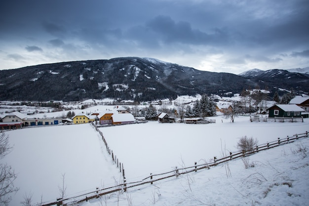Beautiful landscape of austrian town in valley at alps covered by snow