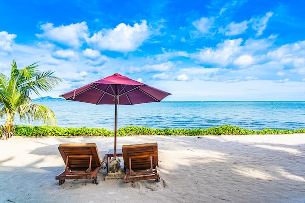 Beautiful landscape of beach sea ocean with empty chair deck and umbrella nearly coconut palm tree with white cloud and blue sky