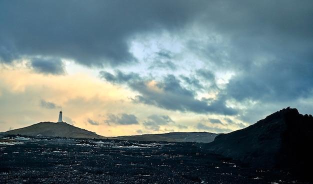 Красивый пейзаж, пустыня с черным вулканическим песком, вдалеке маяк на фоне заката, небо затянуто облаками.
