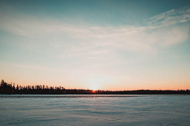 Beautiful landscape of frozen lake at sunrise