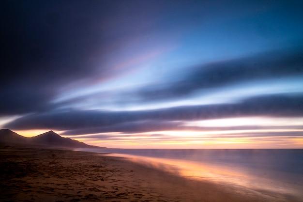 山と色付きの曇りの夕日の間にビーチで長時間露光の美しい風景