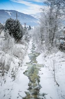 雪に覆われた森の速い渓流の美しい風景