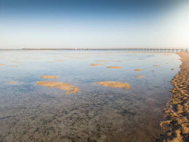 Красивый пейзаж длинного пирса и песчаного пляжа в океане при свете заката