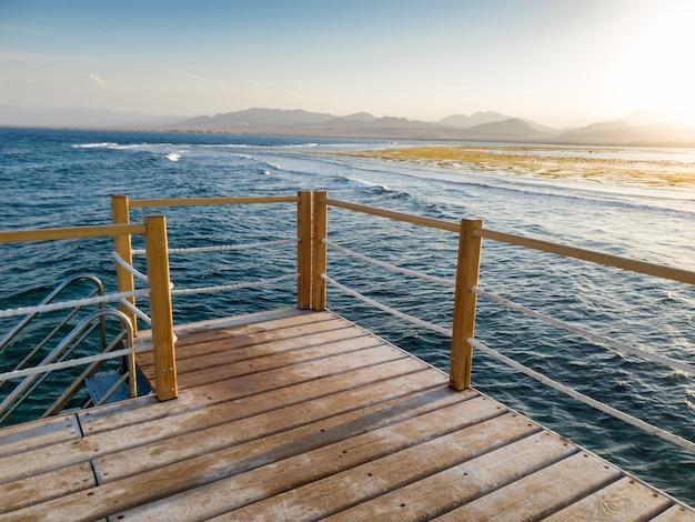 Красивый пейзаж длинной деревянной пристани и спокойных морских волн на фоне заката и гор