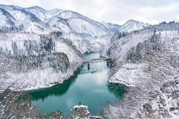 福島の冬の只見川を渡る只見線列車の美しい風景
