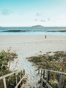 Красивый пейзаж пляжа во время заката с человеком, тренирующимся