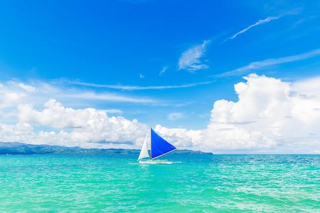 Красивый пейзаж тропического пляжа на острове боракай, филиппины. парусник в море. вид на природу. концепция летних каникул.