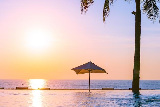 ホテルのリゾートのパラソルとデッキチェア付きの美しい風景屋外スイミングプール