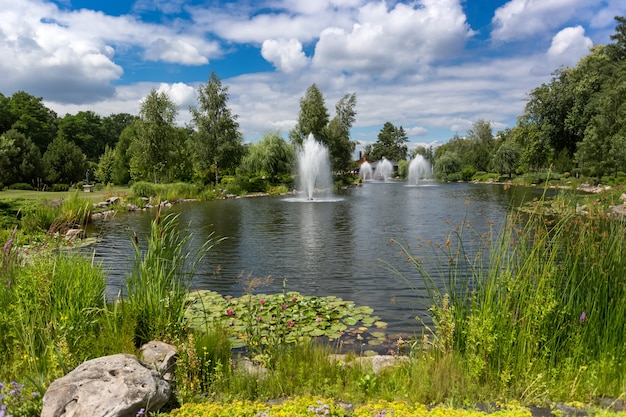 Beautiful landscape of pond with fountains at park at sunny day