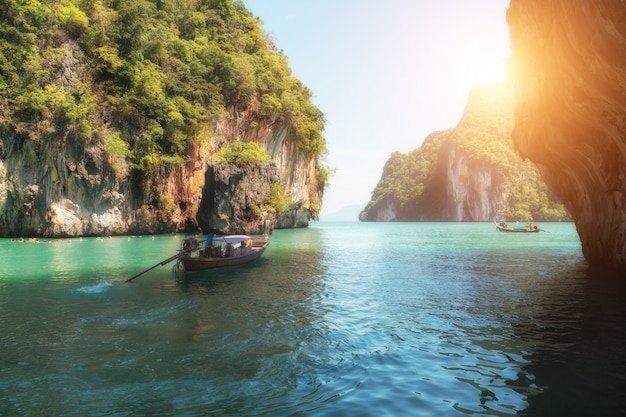 Beautiful landscape of rocks mountain and crystal clear sea with longtail boat at phuket, thailand.