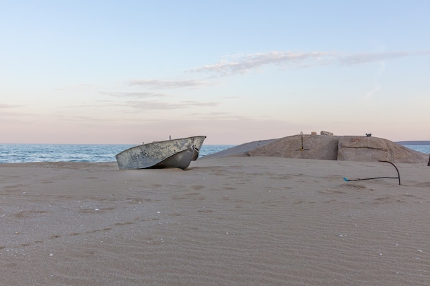 Beautiful landscape of rusty boat on the beach in sunrise. vintage boat in the seashore
