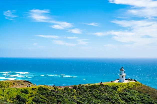 Красивый пейзажный пейзаж с зелеными горами, голубым небом и маяком, историческим зданием. мыс рейнга, северный остров, новая зеландия.
