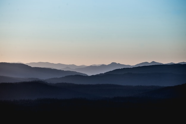 분홍빛이 도는 하늘 아래 산과 언덕의 아름다운 풍경 샷