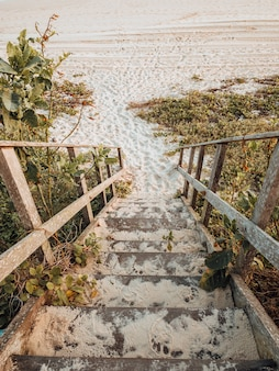 Beautiful landscape shot of the stairs to the beach with golden sunset colors