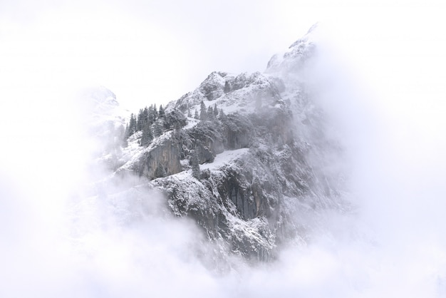 Beautiful landscape of snowy mountains and fog between peaks.