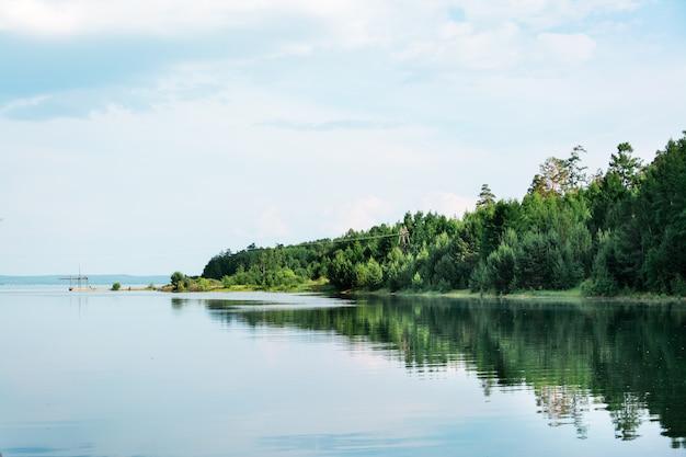 美しい風景-川の春の洪水。森のある海岸は水で溢れています