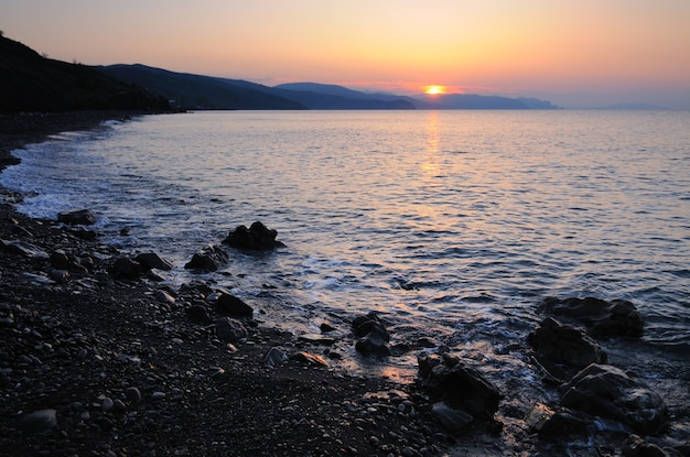 Beautiful landscape, sunset by the sea, sun rises from behind the mountains, beach is strewn with stones