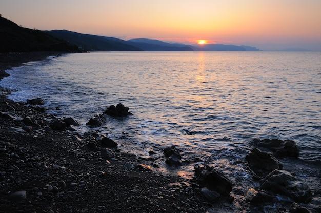 아름다운 풍경, 바다 일몰, 태양이 산 뒤에서 떠오르고 해변은 돌로 흩어져 있습니다.