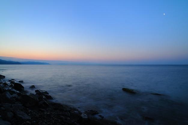 바다 태양이 산 뒤에서 떠오르는 아름다운 풍경 일몰