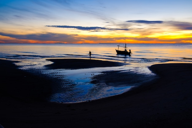Beautiful landscape view of nature in the morning sunrise with silhouette fishing boat on the beach and orange and blue sky in thailand