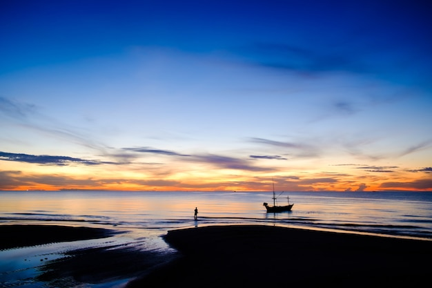 Beautiful landscape view of nature in the morning sunrise with silhouette fishing boat on the beach and orange and blue sky
