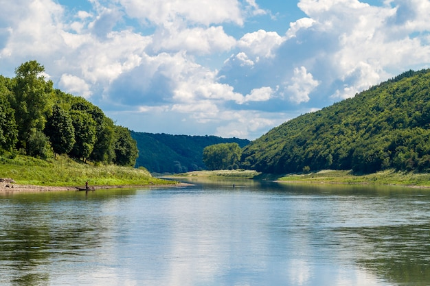 Beautiful landscape with blue water in a river and green trees in forest on mountain hills