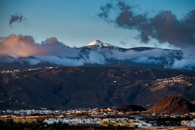 Красивый пейзаж с ночными огнями города и большой вулканической горой