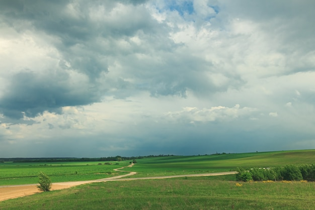 Beautiful landscape with green field and clouds.