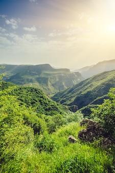 緑の山々と夕日の壮大な曇り空の美しい風景