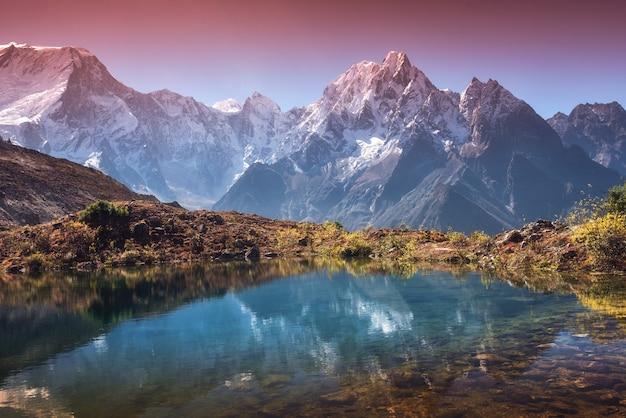 눈 덮인 봉우리와 높은 산이 있는 아름다운 풍경, 하늘은 호수에 반영됩니다. 일출에 물에 반사와 산 계곡입니다. 네팔. 히말라야 산맥이 있는 놀라운 장면. 자연