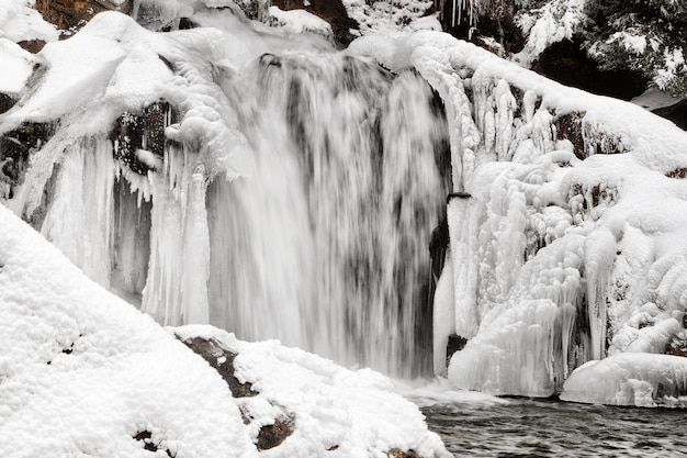 Beautiful landscape with mountain stream and waterfall on winter day