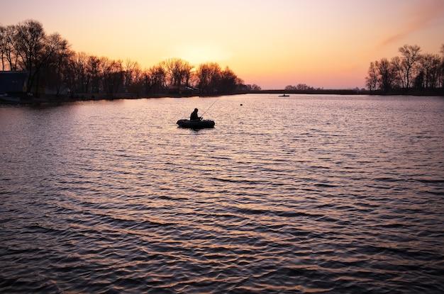 オレンジ色の日の出、湖、ボートに乗って漁師と美しい風景