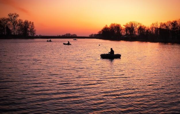 Красивый пейзаж с оранжевым восходом солнца, озером и рыбаками в лодках