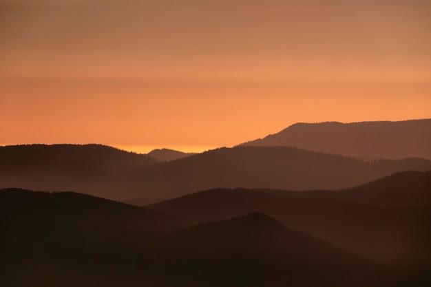 오렌지 하늘 일출 산맥의 실루엣과 아름 다운 풍경입니다.