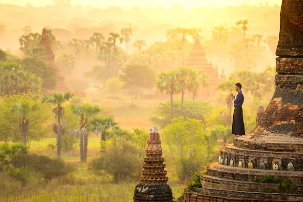 The beautiful landscape of young man praying on temple myanmar style and enjoying at sunri