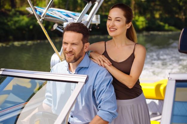 美しい景色。魅力的な若いカップルがボートに乗って景色を楽しみながら、女性が夫に手を置いて