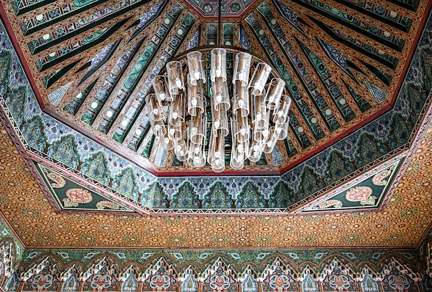 Beautiful large chandelier on the ceiling in a traditional oriental style with many details and ornaments.