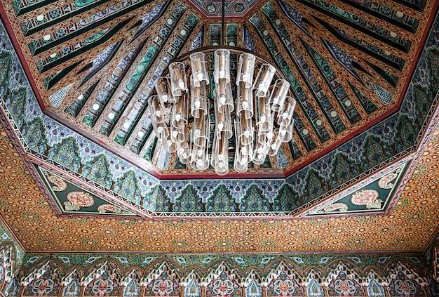 많은 세부 사항과 장식품이있는 전통적인 동양 스타일의 천장에 아름다운 대형 샹들리에.