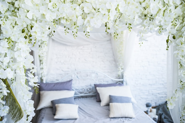 Beautiful large double bed with white textile decorated with flower garlands stands in an empty bedroom