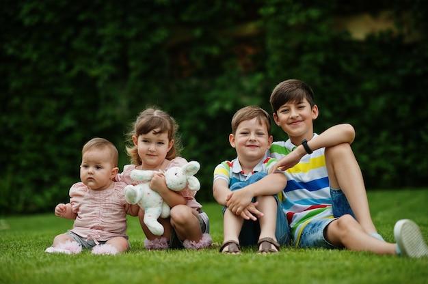 中庭の緑の芝生に座っている4人の子供を持つ美しい大家族。