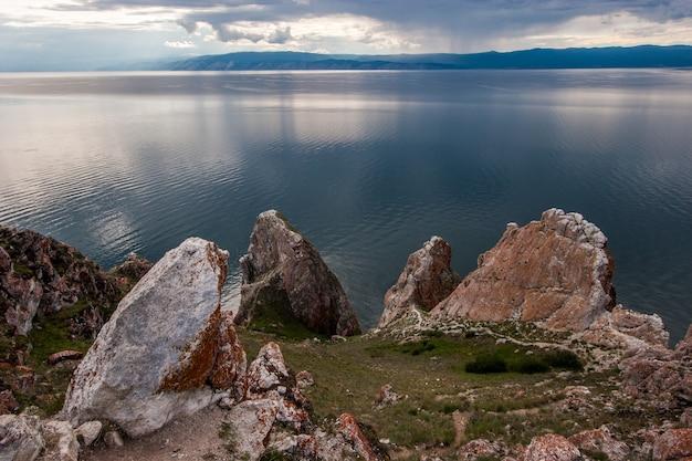 Красивые большие камни на фоне байкала на камнях красный мох в небе облака