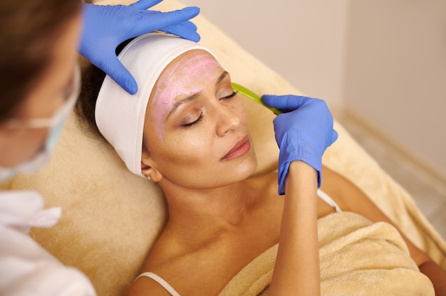 Beautiful latin american woman with a pink facial mask lying in beauty health spa center