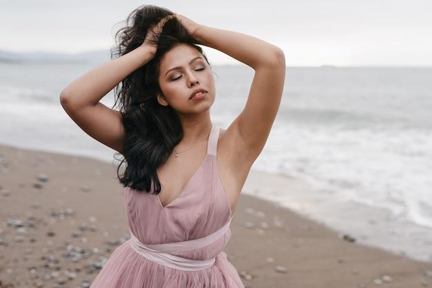 ピンクのバレエ ドレスに身を包んだビーチの美しい夕日でポーズをとって長い黒い棒を持つ美しいラテンの女の子