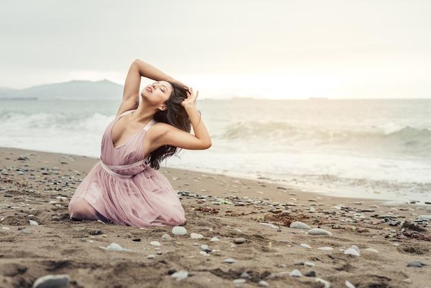 ピンクのバレエ ドレスに身を包んだビーチの美しい夕日にひざまずいてポーズをとって長い黒い棒を持つ美しいラテンの女の子