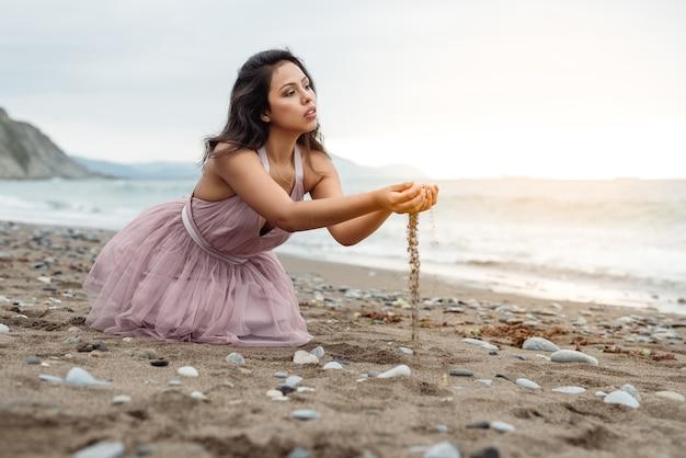 ピンクのバレエ ドレスを着たビーチの美しい夕日に、床に膝をついてポーズをとり、砂で遊んでいる長い黒い棒を持つ美しいラテンの女の子
