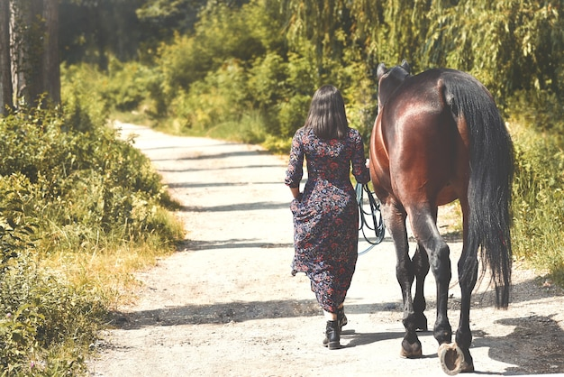 Beautiful latin woman in dress and her lovely horse walk in the forest. back view. love animals concept. love horses