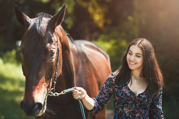 Beautiful latin woman in dress and her lovely horse walk in the forest. love animals concept. love horses